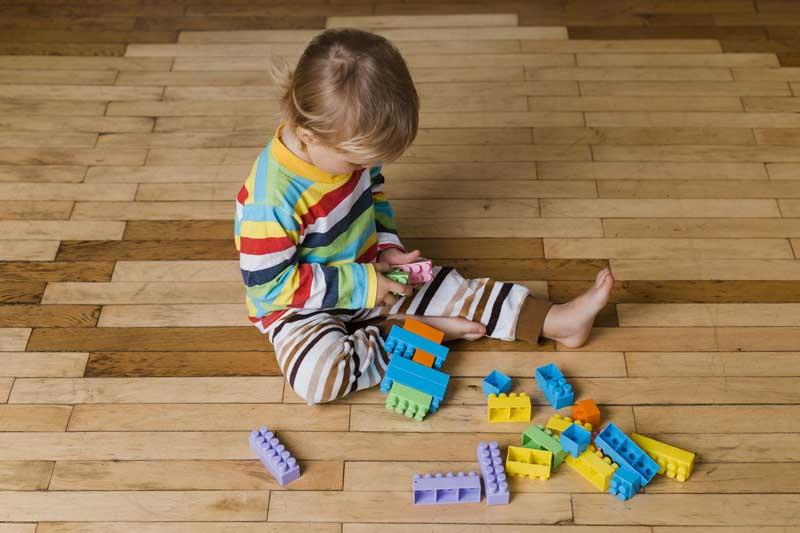 دانلود عکس باکیفیت پسر بچه در حال بازی با اسباب بازی خانه سازی