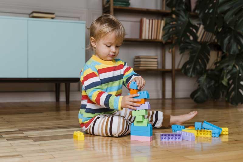 عکس باکیفیت پسر بچه در حال بازی با اسباب بازی خانه سازی