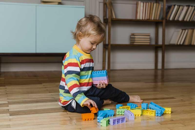 عکس با کیفیت پسر بچه در حال بازی با اسباب بازی خانه سازی