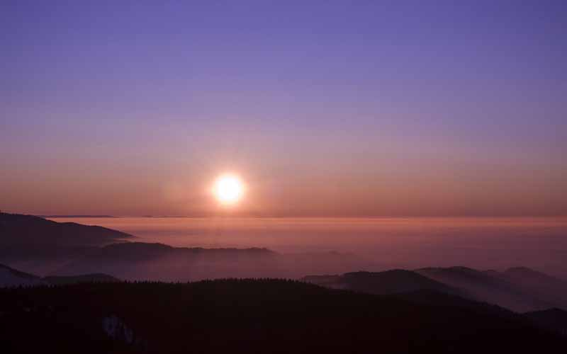تصویر باکیفیت طلوع خورشید بالای مه